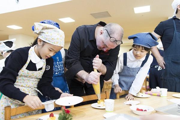 コルビシェフと一緒にケーキ作りに励む子どもたち